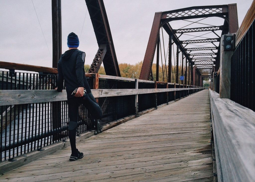 Man standing on a bridge preparing to run