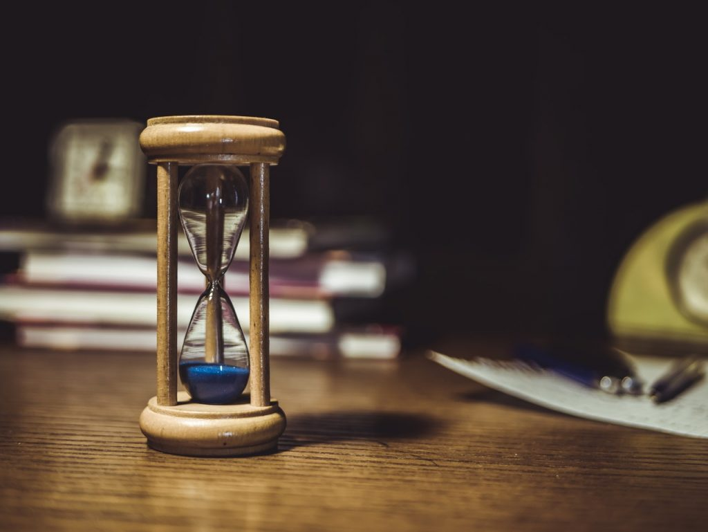 Brown hourglass on brown wooden table